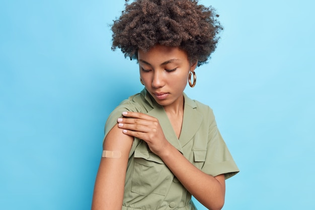 Serious afro american woman shows arm after vaccine injection wears adhesive tape dressed in t shirt isolated over blue wall
