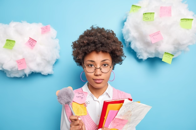 Serious afro american woman student holds papers notebook pen wears rounded spectacles prepares for examination session isolated over blue wall with clouds above
