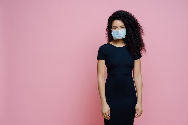 Serious afro american woman wears disposable medical mask on face