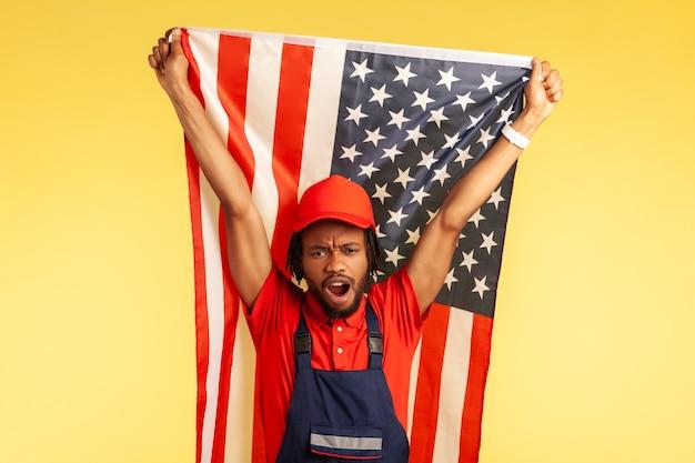 制服を着た真面目なアフリカ系アメリカ人労働者。ドレッドヘアがアメリカの国旗を掲げ、自由と独立を祝って叫んでいます。黄色の背景に分離された屋内スタジオショット