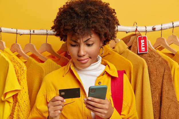 Серьезная афро-женщина использует кредитную карту с мобильным телефоном для покупок в интернете в универмаге, покупает одежду на распродажах, одетая в модную желтую рубашку, стоит против разной одежды на вешалках.