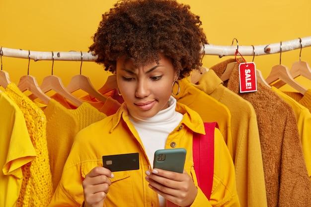 La donna afro seria utilizza la carta di credito con il telefono cellulare per lo shopping online nei grandi magazzini, acquista vestiti in saldo, vestita con una camicia gialla alla moda, si erge contro vestiti diversi sui ganci