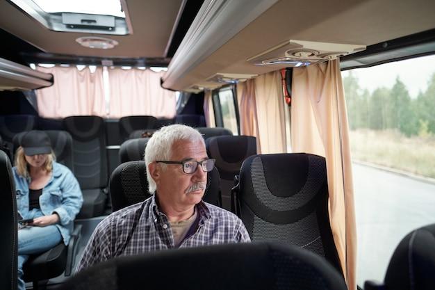 Серьезный пожилой мужчина в очках сидит у окна в автобусе