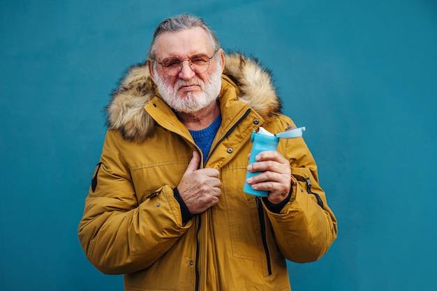アウターウェアの飲料水で深刻な老人。