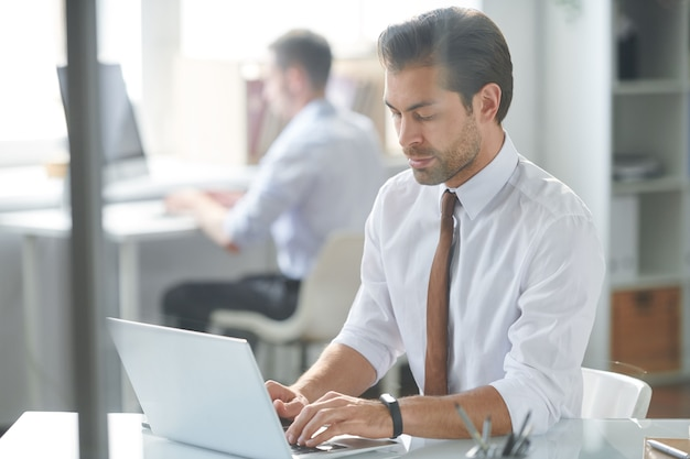 Serious analyst entering upgraded information while sitting by workplace in front of laptop