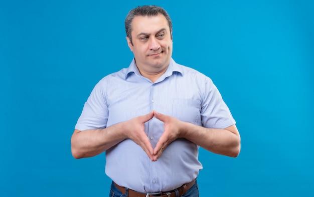 厳密に青い背景に手を一緒に保つことを探している青い垂直ストライプシャツで深刻で怒っている中年男