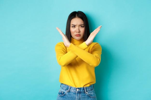 Серьезная и напористая кореянка показывает жест крест-стоп, хмурится и говорит «нет», запрещает действия, не одобряет что-то плохое, стоя на синем фоне.