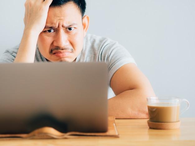 Серьезное и скучное лицо человека работает на ноутбуке.