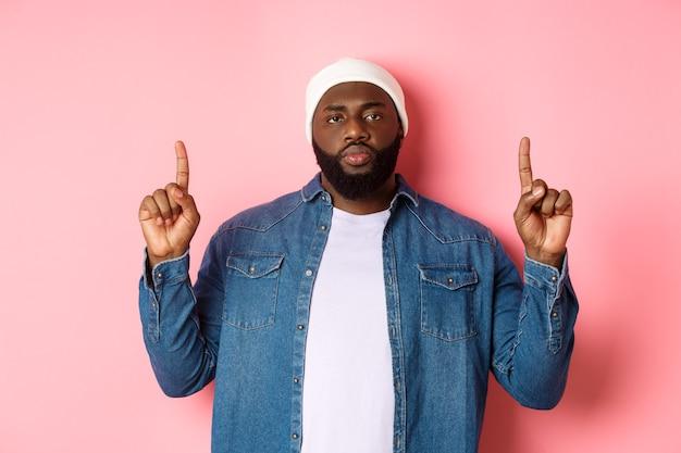Серьезный и обеспокоенный темнокожий мужчина с бородой, указывая пальцами вверх