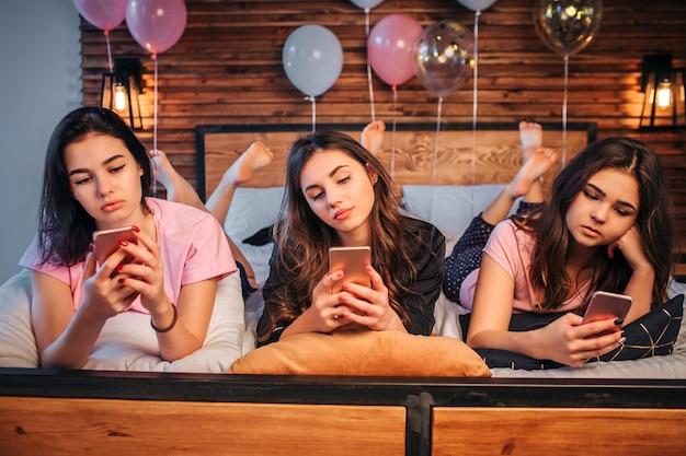 방에 침대에 누워 심각하고 바쁜 oyung 여성. 그들은 전화를 들고 그들을 본다. 여자애들은 슬프고 집중되어 있습니다.