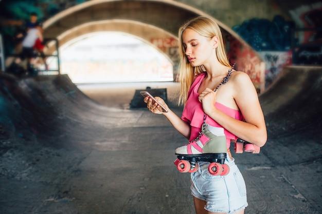 진지하고 집중된 소녀가 서서 전화를 손에 들고 있습니다. 또한 그녀는 어깨에 매달린 롤러를 들고 있습니다. 그녀는 전화를 찾고 있습니다. 그녀는 전화를 기다리고 있다