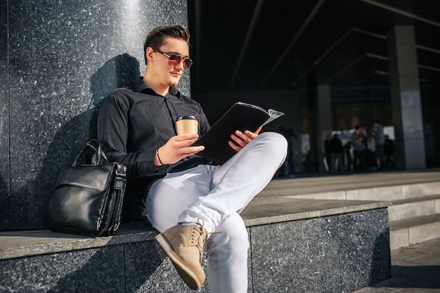 진지하고 집중된 남자가 계단에 앉아서 일기를 읽습니다. 그는 손에 커피 한잔이있다. 남자는 안경을 통해 본다. 그는 한쪽 다리를 다른 쪽 다리에 고정시킵니다.