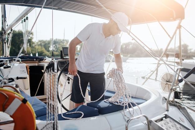 Серьезный и сосредоточенный матрос стоит на яхте