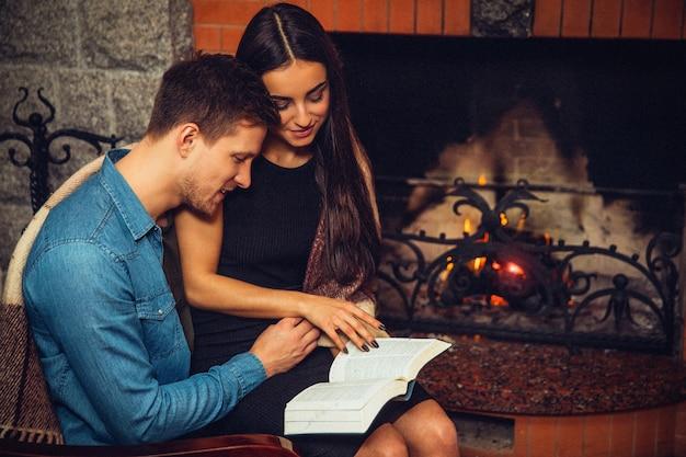 深刻で集中した若い男性と女性が暖炉のそばで一緒に座っています。彼らは開いた本を読んだ。手でタッチページをモデル化します。