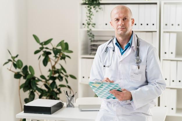클립 보드와 펜이 병원에있는 환자 중 한 명에게 처방전을 만드는 진지하고 자신감있는 의사