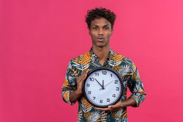 Серьезный и сбитый с толку молодой красивый темнокожий мужчина с вьющимися волосами в рубашке с принтом листьев показывает настенные часы на розовом фоне