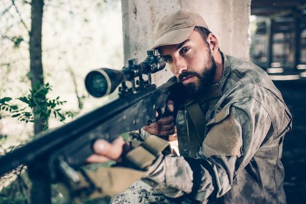 격렬하고 용기있는 전사는 격납고에서 열린 출구 근처에 서 있고 렌즈를 통해 찾고 있습니다. 그는 소총을 사용하여 조준하고 있습니다. 수염 난 남자가 집중되어 있습니다. 그는 기다리고있다.