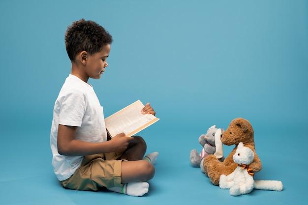 Серьезный и прилежный африканский школьник в повседневной одежде сидит на полу и читает книжку сказок своим игрушкам перед собой