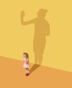 진지하고 공정합니다. 어린 시절과 꿈의 개념. 아이와 노란색 스튜디오 벽에 그림자 개념적 이미지. 어린 소녀는 비즈니스 여성, 사무실 숙녀가되어 경력을 쌓고 싶습니다.