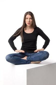 蓮華座に座っている真面目でラフな女性。白い壁に孤立した画像。