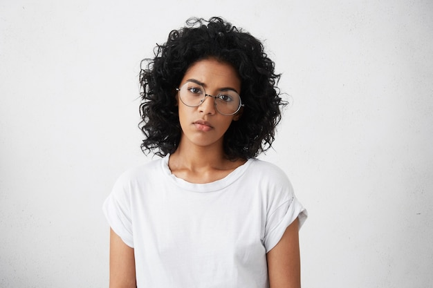 大きなエレガントな眼鏡をかけているアフロのヘアカットを持つ深刻な悲しい黒人女性