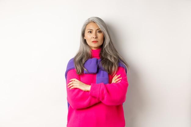 カメラに腹を立て、胸に腕を組んで、白い背景の上に立っている真面目で厳格なアジアの祖母はがっかりしました。