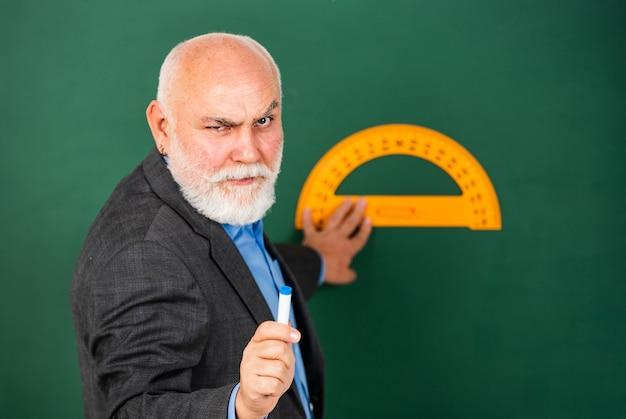 Серьезный и строгий. домашнее обучение. старший учитель использует транспортир. бородатый наставник мужчина рисовать с линейкой на доске. обратно в школу. любимый предмет и дисциплины. обучение в школе.