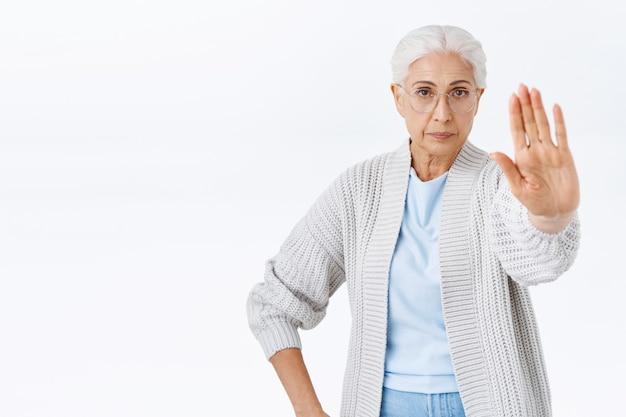 真面目で厳格な老婆、祖母は禁止、腕を前に伸ばして停止、拒否または禁止のジェスチャー、決心して自信を持っているように見える、息子の煙を許可しない、白い壁に立っている