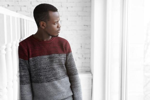 カジュアルで着替えた深刻で思慮深い若い浅黒い男性の建築家