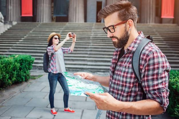 Серьезный и вдумчивый молодой человек стоит снаружи и смотрит на карту, которую держит. женщины турист стоят на спине на снимки городских пейзажей.