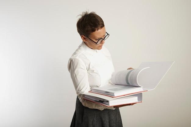 블라우스와 치마에 심각하고 불행한 찾고 젊은 여성 교사는 흰색에 고립 된 두꺼운 바인더에서 페이지를 읽고 있습니다