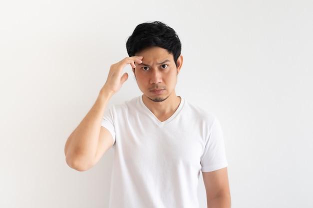 深刻で動揺した男は白い壁に分離された白いtシャツを着ています