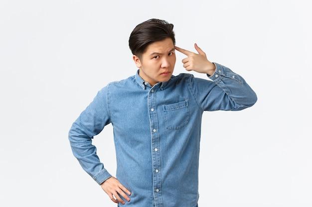 Uomo asiatico arrabbiato serio che guarda con sgomento il dipendente, rimprovera la persona che fa uno stupido errore, tocca la tempia con il dito e fissa frustrato, in piedi sfondo bianco sconvolto.