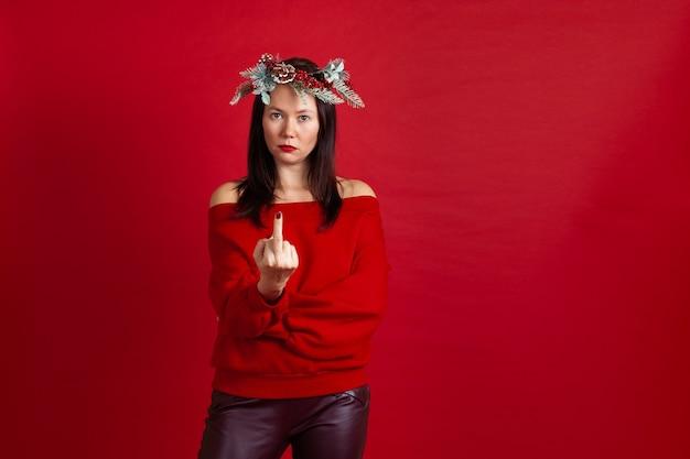 Серьезная злая азиатская женщина в рождественском венке показывает средний палец
