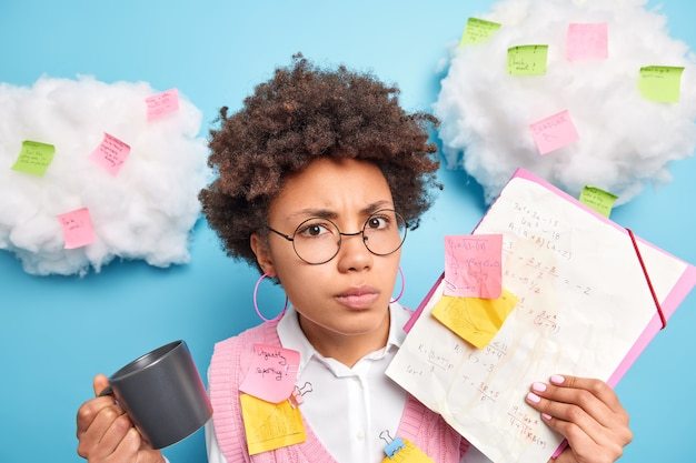 Serious angry displeased schoolgirl with afro hair prepares for exam in maths makes notes tries to remember formulas drinks coffee wears round spectacles poses against blue wall stickers around