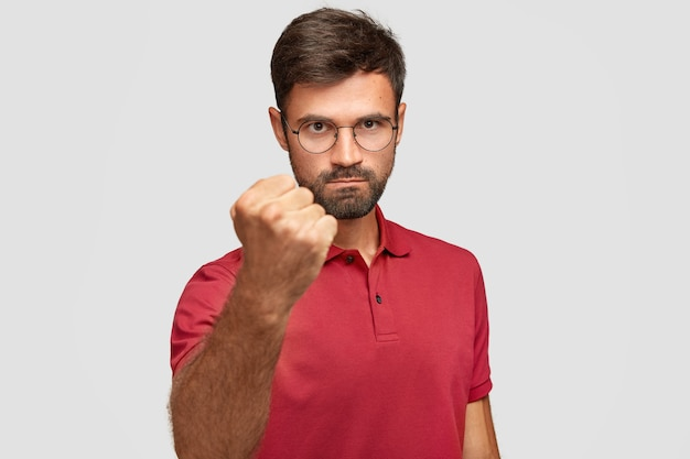 Serious angry male shows fist, ready for fight or challenge, has stern expression, wears casual red t-shirt, poses against white wall. aggressive young man gestures indoor. body language concept