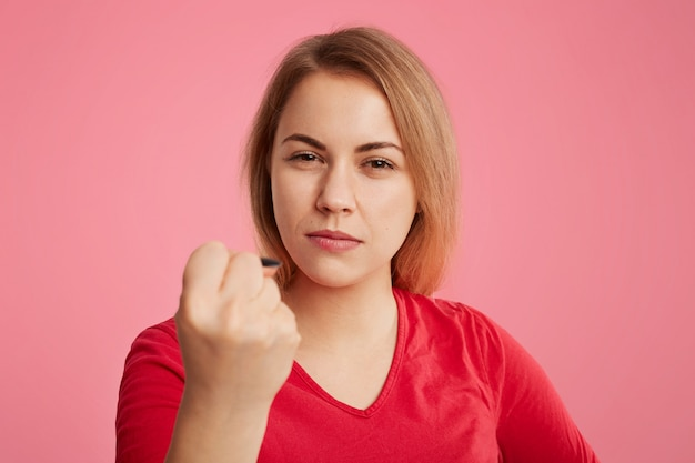 Serious angry woman puts up fist as tries to warn you, dressed in red sweater