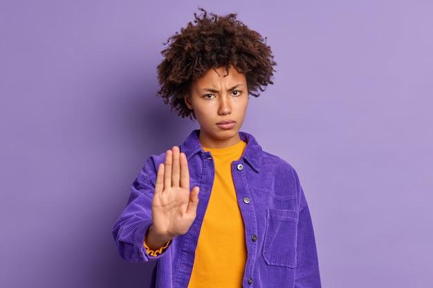 深刻なイライラする暗い肌のアフリカ系アメリカ人の女性は、手のひらを停止ジェスチャーで保ち、彼女の外見を気にしないように求めます。紫色のジャケットを着て、制限または拒否を表現します。近づかないでください