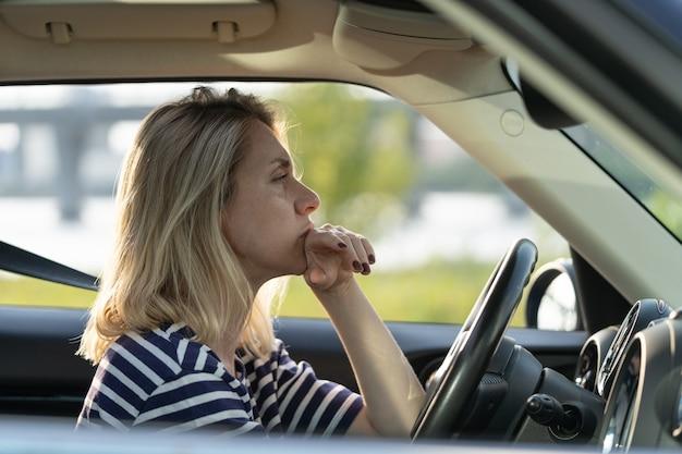 교통 체증에서 기다리는 중년의 잠겨있는 슬픈 여성 운전사를 운전하는 심각한 불안한 여성