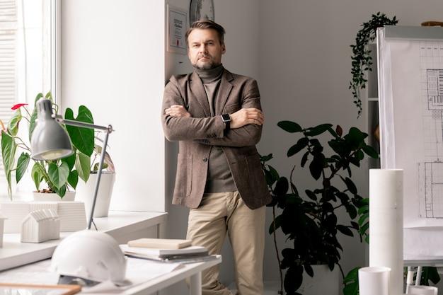 Серьезный архитектор или инженер в официальной одежде, стоящий на рабочем месте у окна перед камерой