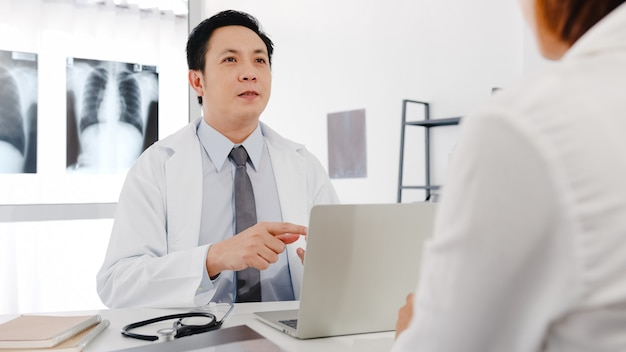 Serious asia male doctor in white medical uniform using computer laptop is delivering great news talk discuss results