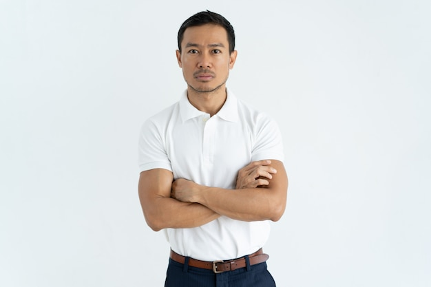 Serious asian businessman in white tshirt looking at camera