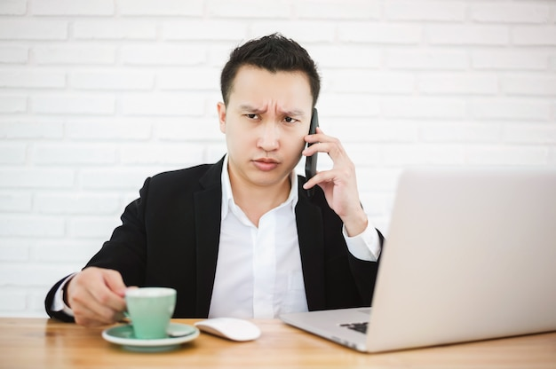 Serious asian businessman working with laptop in the modern office, talking on the phone with his hand still holding a cup of coffee.