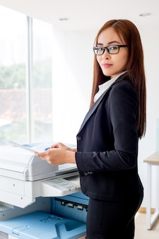 Serious asian businesswoman copying document