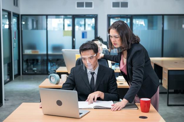 Серьезные азиатские женщины-исполнительные консультанты с коллегой-мужчиной в защитной маске, работающей с ноутбуком за столом в современном офисе