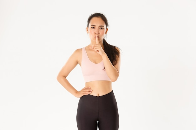 Serious asian female gym instructor, coach demand discipline in fitness class, shushing with finger pressed to lips, stay quiet, white background.