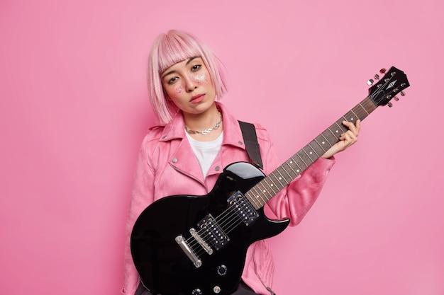 Серьезная азиатская музыкантша смотрит прямо, наклоняет голову, стрижет розовые волосы, позирует с электроакустической гитарой, одетая в модную одежду, позирует в помещении, проводит свободное время в хобби.