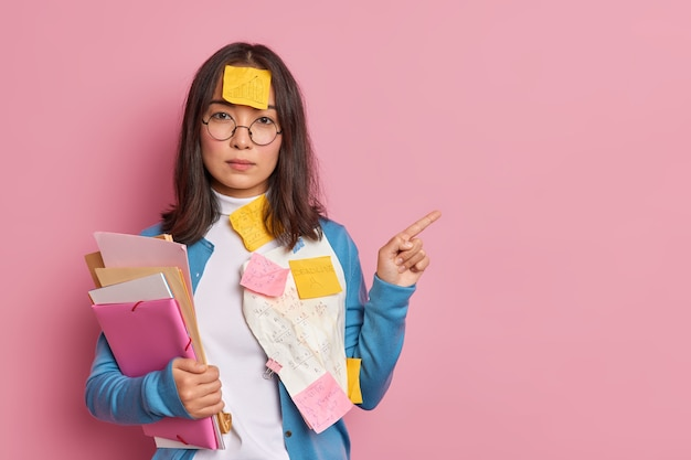Serious asian female office worker holds files stuck with sticky notes written information points aside shows something at blank space wears round spectacles.