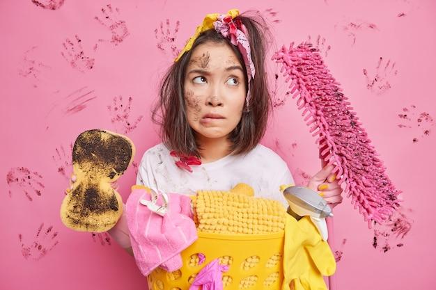 ピンクの壁に隔離された洗濯物の洗面器の近くのアパートのスタンドを掃除した後、深刻なアジアの主婦がどこかに集中した唇を噛む汚れたモップと床を保持します