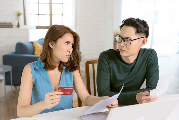 家で一緒に座っているステートメントユーティリティの請求書を分析するチェックしている深刻なアジアの夫。